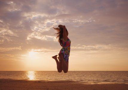 夕方の海辺で飛び跳ねる女性