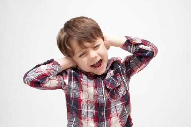 耳を塞ぐ少年の画像