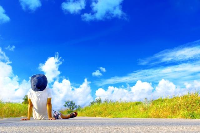 道に座って青空を眺める男性