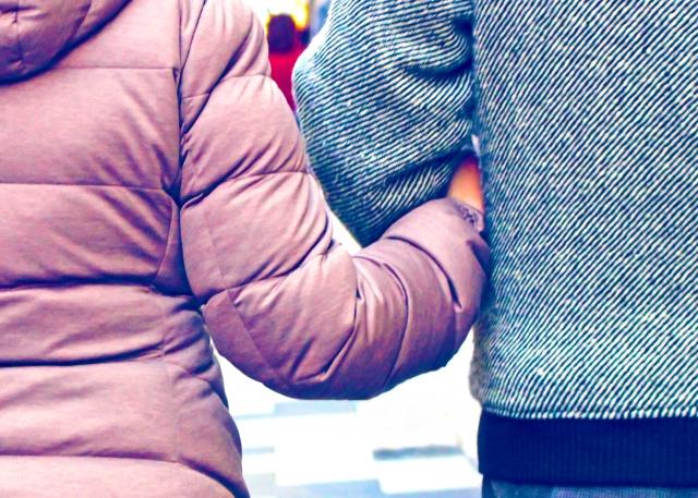 腕を組むカップルの画像