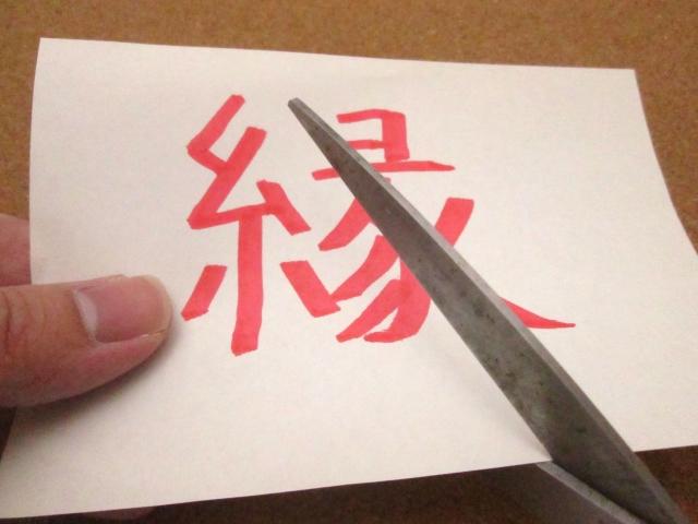 紙に書かれた縁をはさみで切っている