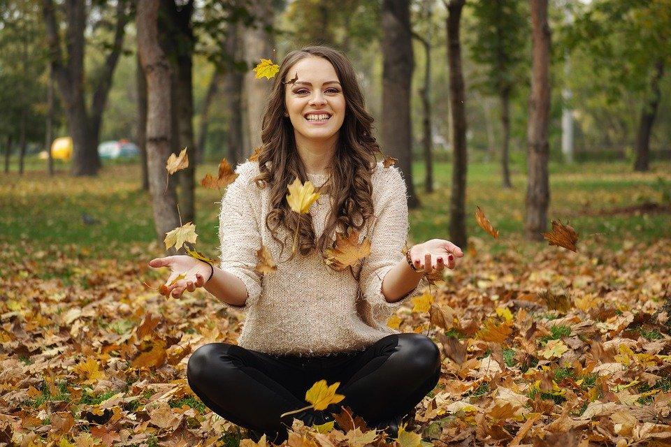 落ち葉を投げる笑顔の女性
