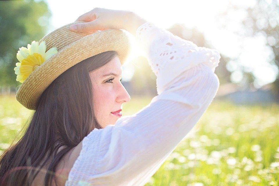 光を見つめて微笑む女性