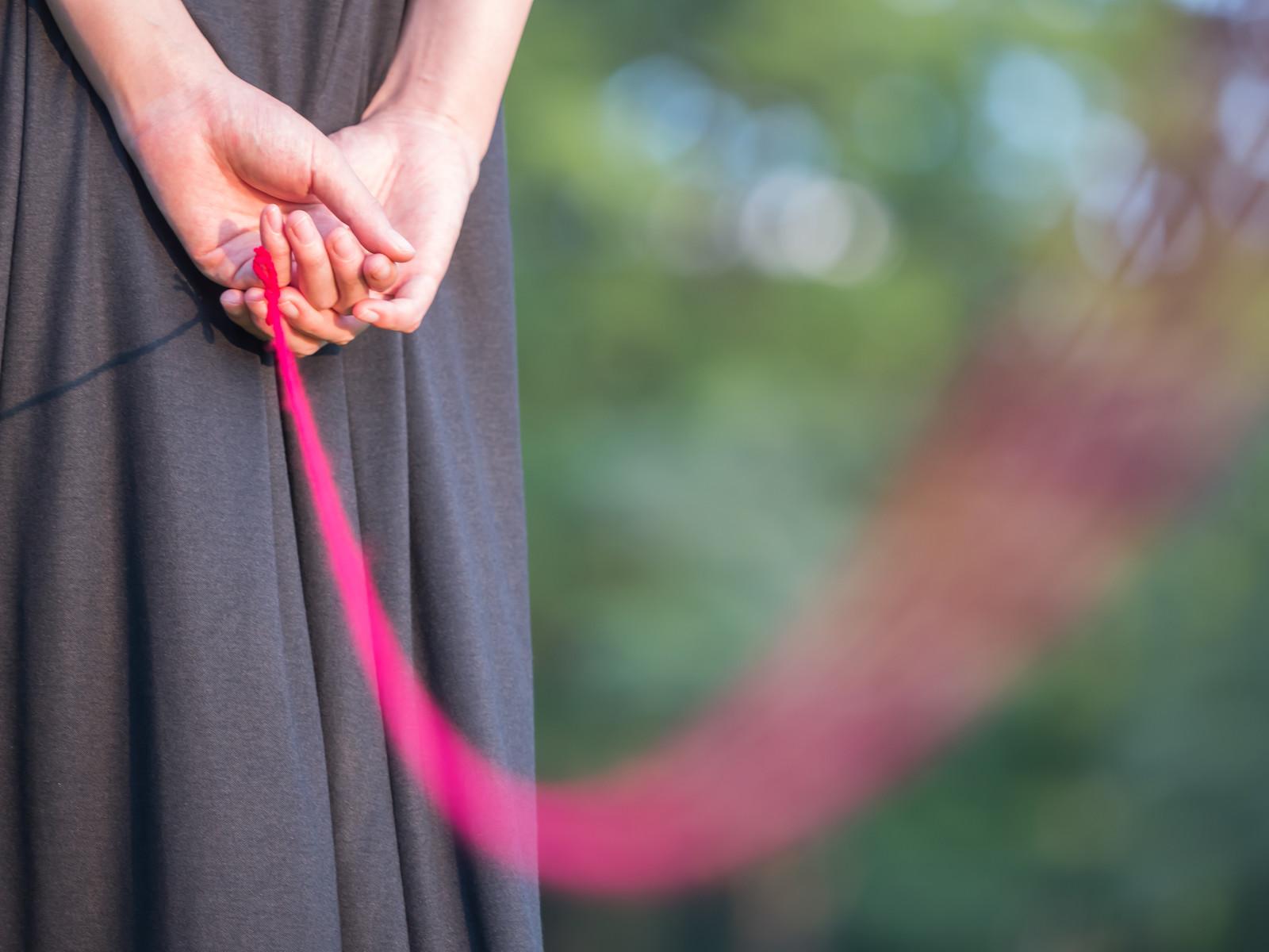 赤い糸でつながれた女性