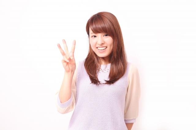 指を三つ立てて微笑む女性