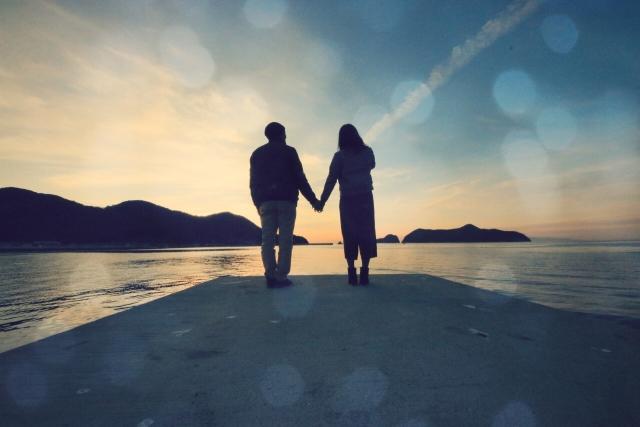 朝方の海岸で背を向けて手を繋ぐカップル