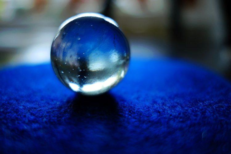 青色の敷物の上に乗る透明なビー玉