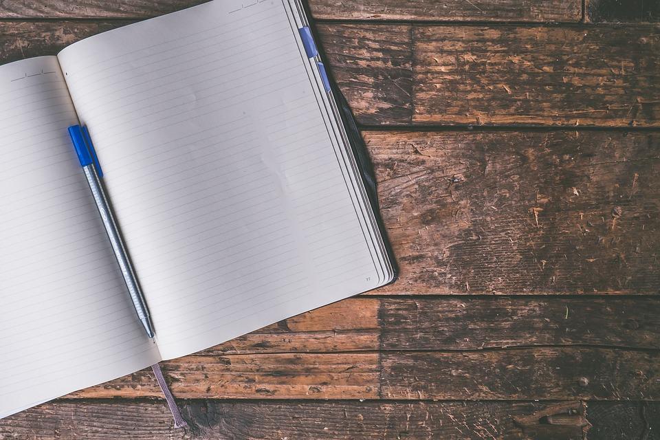 まっさらなノートとペンが机に乗っている