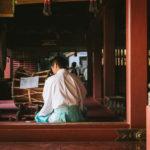 社殿で笛を吹く神主の画像