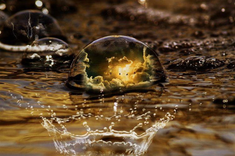 水面に落ちる水滴が朝日を写している