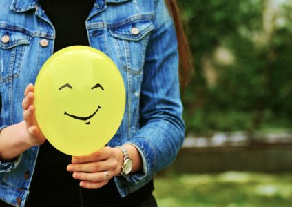 黄色い笑顔のバルーンを持った女性