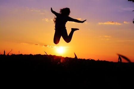 いいことがあって夕陽に向かってジャンプしている女性